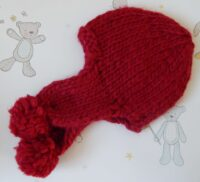 child's handknitted red chunky hat with pompoms